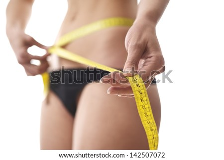 young woman dieting and contemplating weight loss measuring waist with tape on white background - stock photo