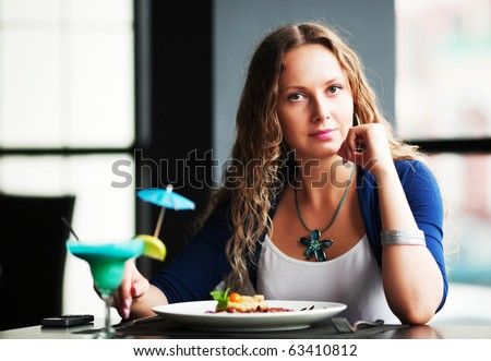 Young woman dining at a restaurant. - stock photo