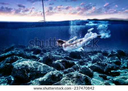 Young woman diving in sunset time, enjoying swimming underwater, wearing long white dress, luxury summer vacation, freedom and pleasure concept - stock photo