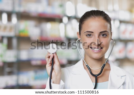 Young woman doctor holding stethoscope in pharmacy - stock photo