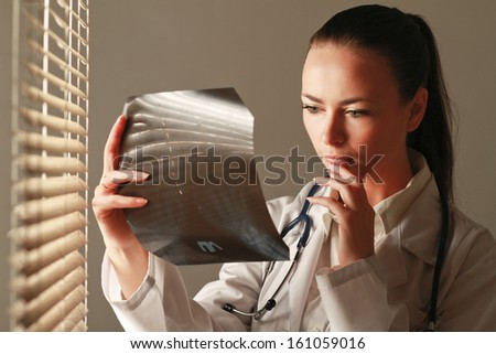 Young woman doctor  is standing near window and examining x-ray - stock photo