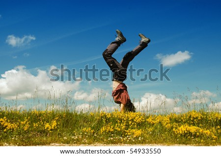 Young woman doing a cartwheel in a meadow - stock photo