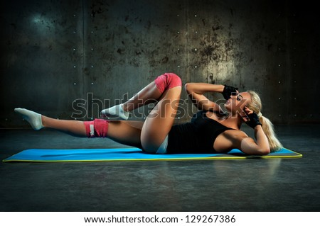 Young woman doing abdominal exercises. - stock photo