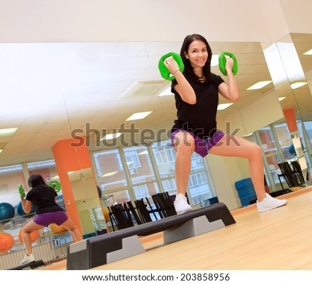 Young woman doing exercise with dumbbells - stock photo