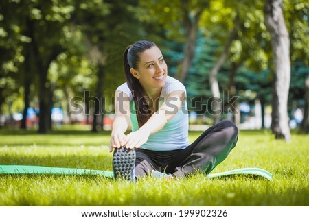 young woman doing exercises in the park - stock photo