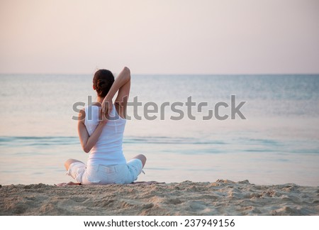 Young woman doing exercises sitting on sea coast at dawn - stock photo