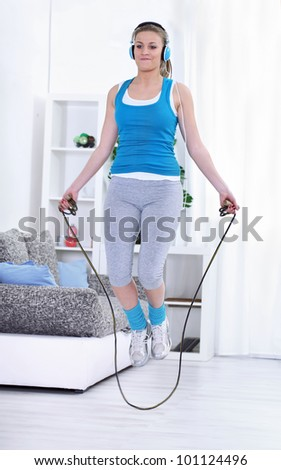 Young woman doing exercises with a jumping rope. - stock photo