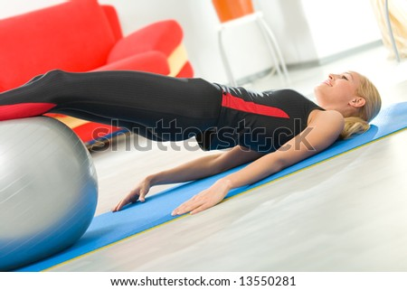 Young woman doing exercises with fitness pilates ball at home - stock photo