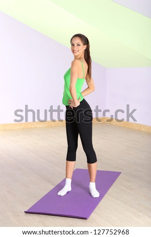 Young woman doing fitness exercises at gym