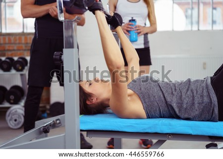 Young woman doing fitness training in a gym lifting weights raising a barbell above her head watched by an instructor - stock photo