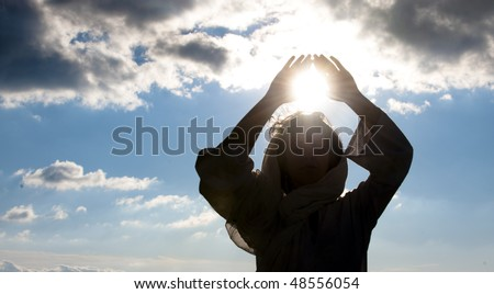 Young woman doing meditation with sun in her hands. - stock photo