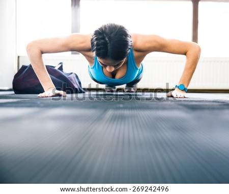Young woman doing push ups at gym - stock photo