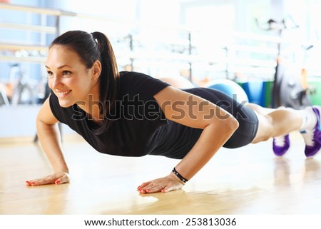 Young woman doing push ups in the gym - stock photo