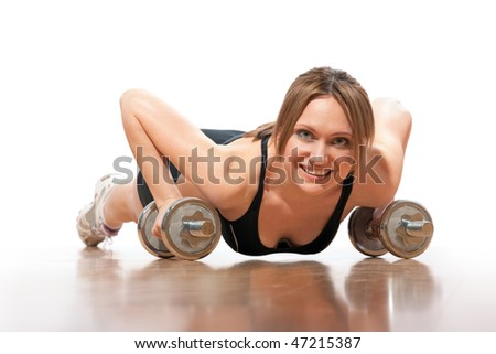young woman doing push-ups on dumbbells
