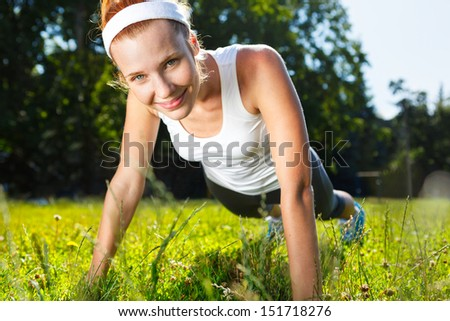 Young woman doing push ups on green grass. - stock photo