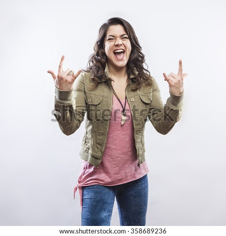 Young woman doing rock horn hand gesture - stock photo