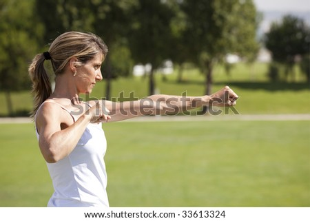 young woman doing some exercise at the park - stock photo