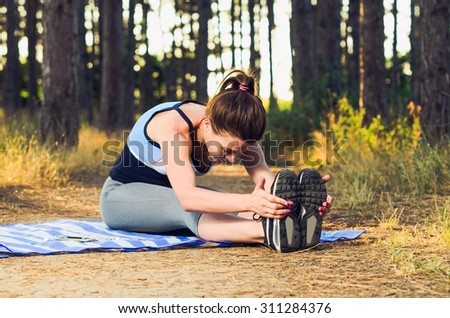 Young woman doing some warm-up exercises before running in the forest. - stock photo