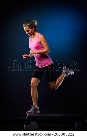 young woman doing step exercises in the gym - stock photo