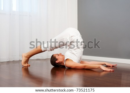 young woman doing stretch yoga on floor - stock photo