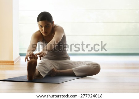 Young woman doing stretching exercise on yoga mat - stock photo