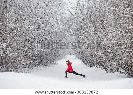 Young woman doing stretching exercises during winter training outside in cold snow weather in park. Trees in the snow. Weather snow cloud. Fitness on the street in the winter. - stock photo