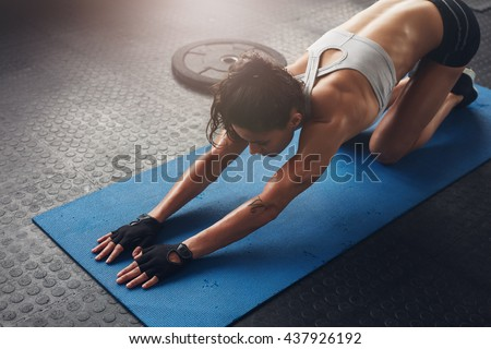 Young woman doing stretching exercises in a health club. Woman on fitness mat doing stretching workout at gym. - stock photo