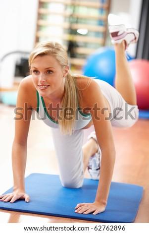 Young Woman Doing Stretching Exercises In Gym - stock photo
