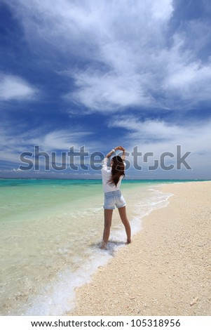 young woman doing stretching exercises on beach - stock photo