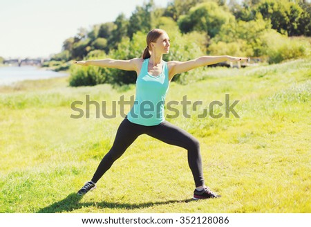 Young woman doing stretching exercises on grass in sunny summer day