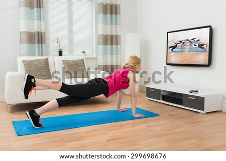 Young Woman Doing Workout While Watching Television In House - stock photo