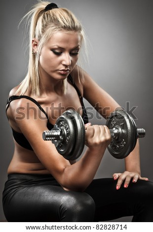 Young woman doing workout with weights, studio shot