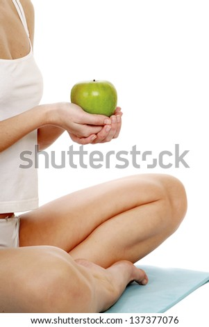 Young woman doing yoga and hold apple , isolated on white background - stock photo