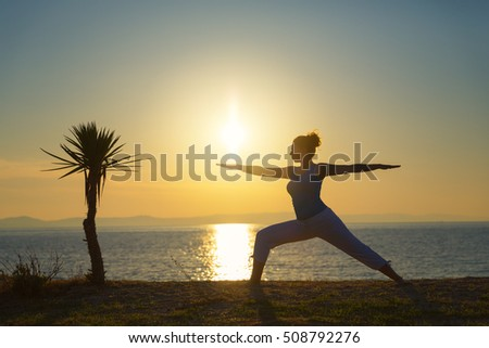 Young woman doing yoga at the beach.