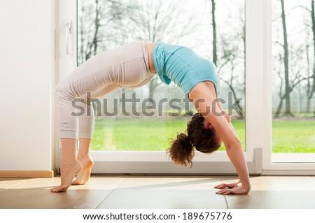 young woman doing yoga bridge pose indoor - stock photo