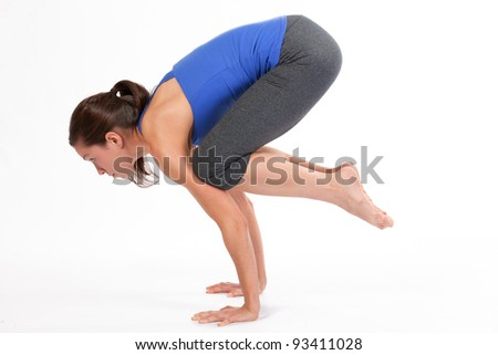 Young woman doing yoga crow pose
