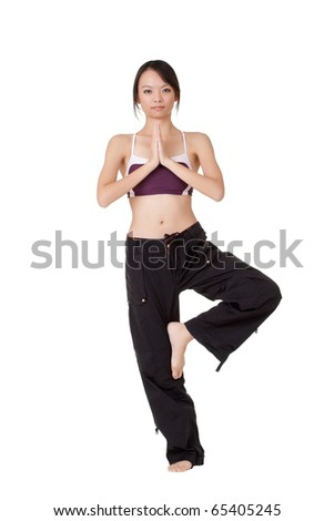 Young woman doing yoga excise by standing on one foot isolated over white. - stock photo
