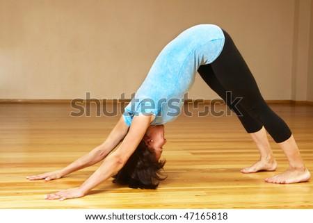 young woman doing yoga exercise indoors - stock photo