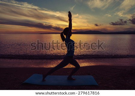 Young woman doing yoga exercise on beach in summer at sunset, concept of healthy lifestyle - stock photo