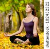 Young woman doing yoga exercises in the autumn city park. Fall - stock photo