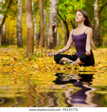 Young woman doing yoga exercises in the autumn city park lake. Fall with mirror in water - stock photo