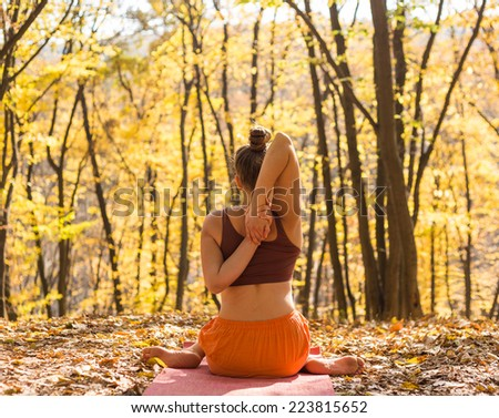 Young woman doing yoga in morning park. Young girl of Caucasian ethnicity outside doing yoga asana in autumn - stock photo