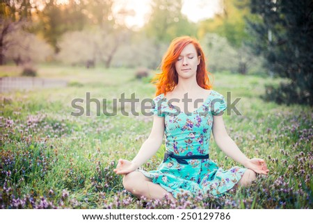 Young woman doing yoga in park at the sunset - stock photo