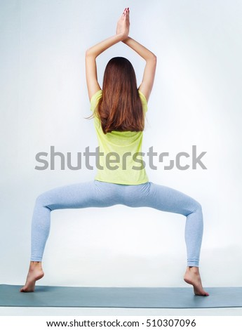 young woman doing yoga, isolated against black studio background