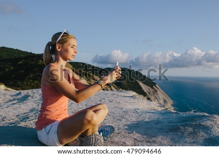 Young woman doing yoga lotus position use mobile phone taking photo on the background mountain peak cliff. Sport lifestyle travel concept
