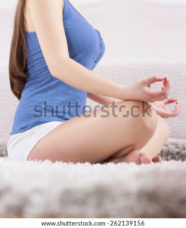 Young Woman Doing Yoga Meditating Relaxing Exercise at home.Healthy Lifestyle in Lotus Posture .Unrecognizable caucasian female practicing meditation on the floor. - stock photo