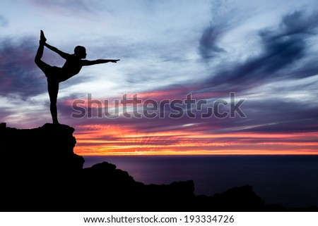 Young woman doing yoga natarajsana, sunset silhouette in mountains over ocean and sky - stock photo
