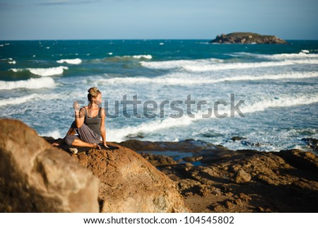 Young woman doing yoga on a rocky seashore - stock photo