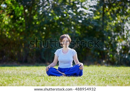 Young woman doing yoga outdoors in tranquil environment of green park on a summer sunny day. Serene relaxed female yoga instructor