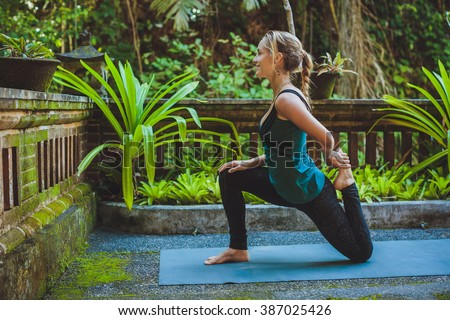 young woman doing yoga outside in natural environment - stock photo